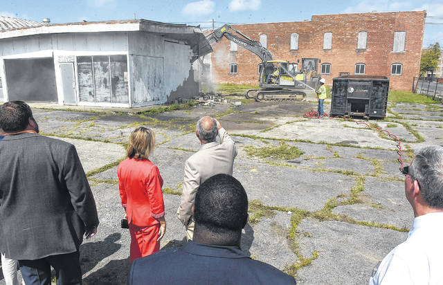 Lima Rotary Club members watch as demolition begins for a downtoown amphitheater site Monday afternoon. The property extends from Spring Street to Elm Street and is bounded by Union Street on the east and the backs of the Main Street buildings on the west.