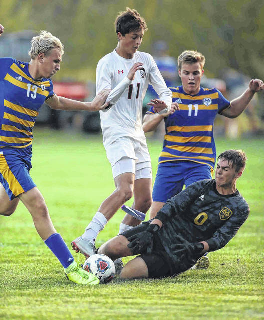 St.Marys' Correy Nelson (on ground) tries to keep the ball out of the after Shawnee's Austin Miller (middle) attempts a shot on goal as St.Marys' Justin Grannan (far left) and St.Marys' Evan Menker (right) is on defense at St.Marys middle school Monday.