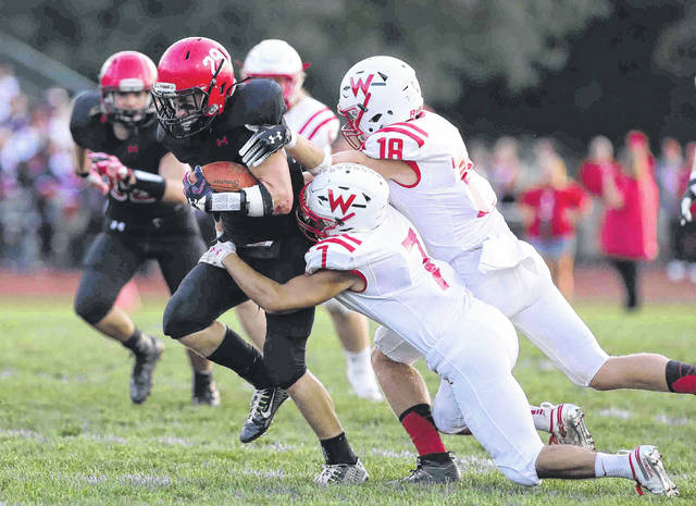 Wapakoneta's Elyjah Roa (7) and Trevor Crow try to bring down Shawnee's Peyton Wilson during Friday night's game at Shawnee. Don Speck | The Lima News