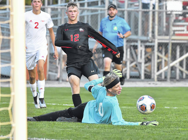 Shawnee's Jacob Miller is a able to get the ball past Wapakoneta's Trey Ware for a goal during Tuesday night's match at Shawnee.