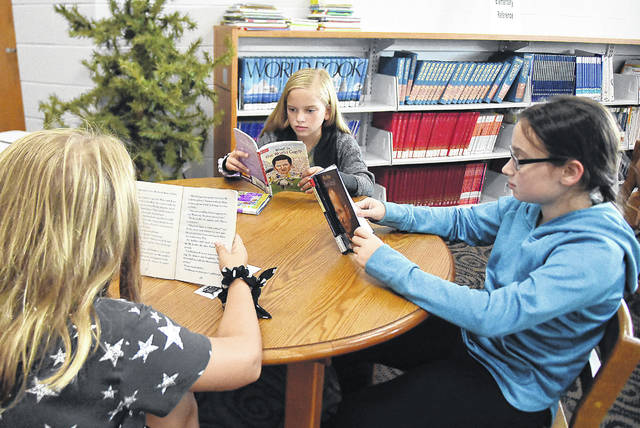Fourth grade students, Nora Gallaspie, 10, center, Naomi Boedicker, 9, and Alexia Post, 9, at Spencerville schools , read books in the library on Thursday.