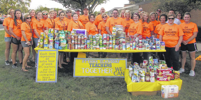 Ottawa and Glanforf elementary teachers and Ottawa-Glandorf High School teachers stand next to over 500 pounds of canned goods they collected that were donated to Ottawa Food Pantry. The canned items represent their work hours that took place outside of their normal school day for one week Aug. 30 to Sept. 6 with the idea of contributintg one non-perishable food item her hour worked.