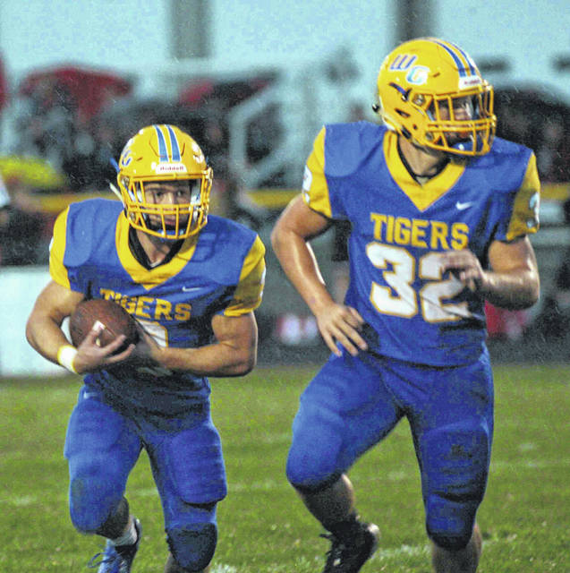 Waynesfield-Goshen running back Joel Rickler follows the block of Kyle Searson during Friday night's game against Upper Scioto Valley at Waynesfield.