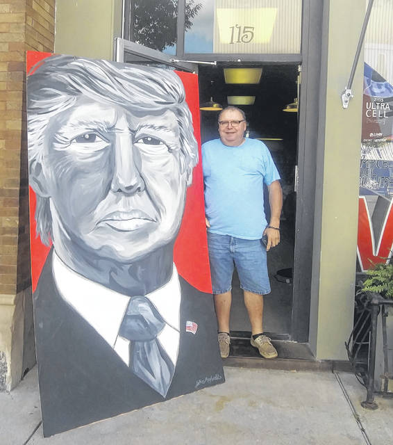 Pictured is Rex Maxwell, owner of Fern Hill Farmhouse, in downtown Wapakoneta next to a painting of President Donald Trump Maxwell's wife painted when Trump was elected.