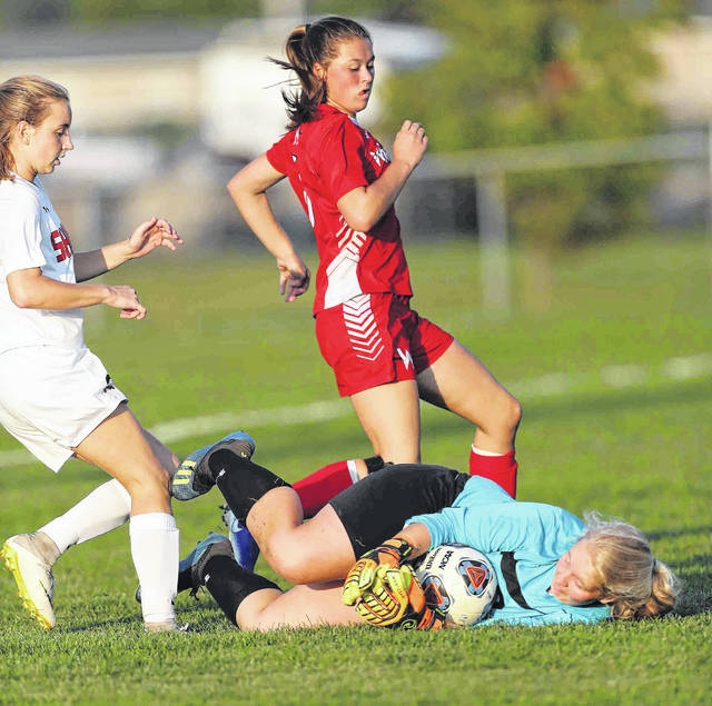 Shawnee goalie Kaelan Swallow protects the ball as Shawnee's Lily Cleaves (left) and Wapakoneta's Katie Lisi avoid the colliding with Swallow at Wapakoneta Monday.