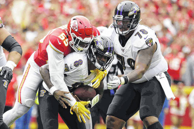 Kansas City Chiefs defensive end Frank Clark (55) sacks Baltimore Ravens quarterback Lamar Jackson (8) with Ravens offensive tackle Orlando Brown Jr. (78) watching during the second half of an NFL football game in Kansas City, Mo., Sunday, Sept. 22, 2019. (AP Photo/Charlie Riedel)
