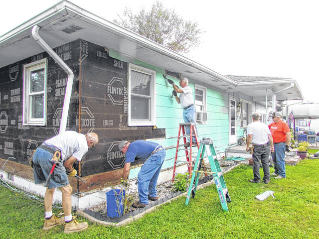 Pictured are Putnam County Habitat for Humanity volunteers working on a siding project on a home in Leipsic Wednesday.
