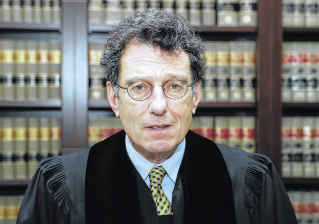 FILE - This Jan. 11, 2018 file photo shows Judge Dan Polster in his office, in Cleveland. Attorneys representing eight drug distributors, pharmacies and retailers facing trial for their roles in the national opioid crisis are seeking to disqualify the federal judge overseeing their cases saying he's shown clear bias in his efforts to obtain a multi-billion dollar global settlement. The motion was filed late Friday, Sept. 13, 2019, in U.S. District Court in Cleveland, where Judge Dan Polster presides over most of the 2,000 lawsuits filed by state, local and tribal governments. Polster has not responded.