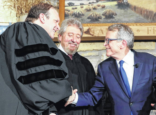 FILE - In this Jan. 14, 2019 file photo, Mike DeWine, right, shakes hands with his son and Ohio Supreme Court Justice Patrick DeWine, left, as Judge Thomas Rose of the U.S. District Court Southern District of Ohio, center, looks on after Mike DeWine was sworn in as the 70th governor of Ohio in Cedarville, Ohio. Patrick DeWine didn't live at the address from which he voted in the last two elections, a citizen alleges in an election complaint. Toledo resident Nathaniel Livingston filed the complaint Sept. 2019, and asked the Hamilton County Elections Board to investigate the 51-year-old DeWine. His spokesman says DeWine intended to return to the home, but he now plans to change his voting address due to the divorce.