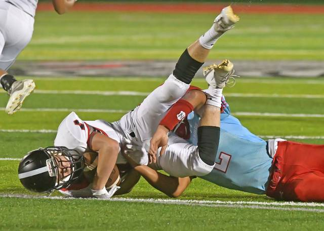 Lima Central Catholic's Shaun Thomas tackles Spencerville's Cody Bockey during Friday night's game at Spartan Stadium.