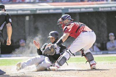 The Indians' Kevin Plawecki tags out the Chicago White Sox's Welington Castillo at home plate during Thursday's game in Cleveland.