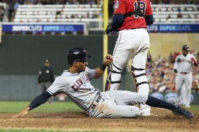Cleveland's Oscar Mercado slides safely into home to score on a sacrifice fly by Yasiel Puig during Friday night's game against Minnesota in Minneapolis. (AP photo)
