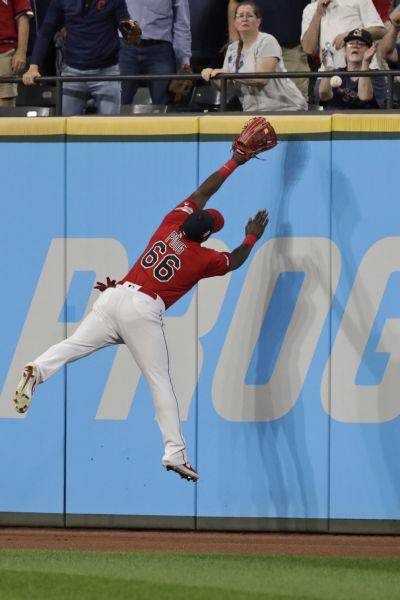 The Indians' Yasiel Puig jumps for but can't prevent a solo home run hit by the Chicago White Sox's Eloy Jimenez during the eighth inning of Tuesday night's game in Cleveland. (AP photo)