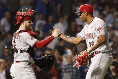 Cincinnati Reds catcher Tucker Barnhart and relief pitcher Raisel Iglesias celebrate the team's 4-2 win Tuesday night against the Cubs in Chicago. (AP photo)