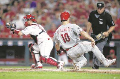 Philadelphia's J.T. Realmuto scores on a sacrifice fly by Rhys Hoskins as Reds catcher Tucker Barnhart takes the throw during Tuesday night's game in Cincinnati.