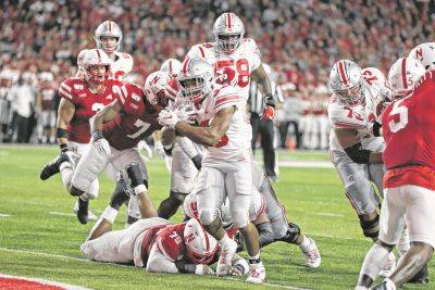 Ohio State running back Master Teague III (33) carries the ball into the end zone past Nebraska defensive lineman Darrion Daniels (79) during Saturday night's game in Lincoln, Neb.