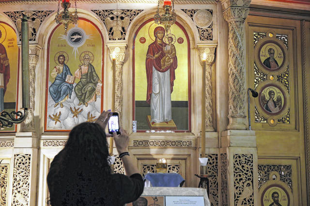 People flock to the painting of the Virgin Mary and take photos of what appears to be a liquid weeping from her eyes in Chicago's Holy Trinity Greek Orthodox Church on Monday. (Stacey Wescott/Chicago Tribune/TNS)