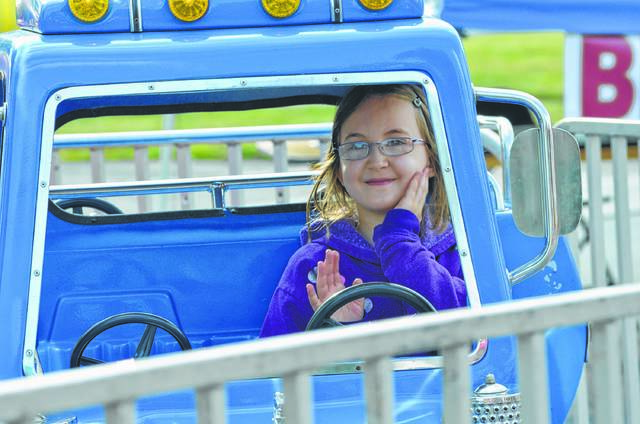 Aviva Prosser, 8, of Oakwood, waves to mother Veronica Prosser while riding the big rig track ride during Kalida Pioneer Days.
