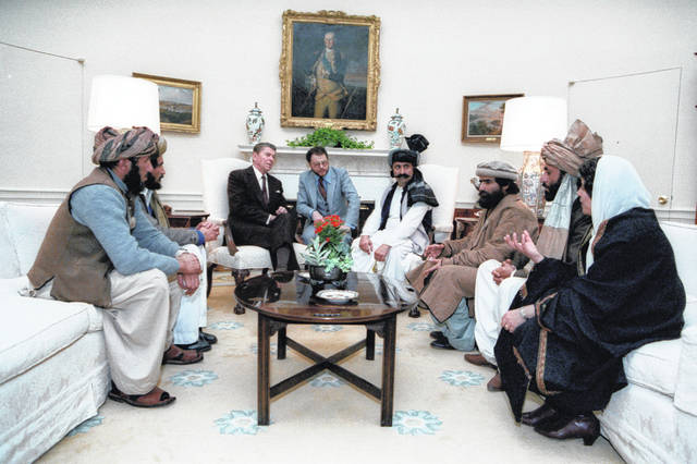 "In this photo courtesy Ronald Reagan Library, then President Ronald Reagan meets with Afghan ""freedom fighters"" on Feb. 2, 1983, in the Oval Office of the White House in Washington, to discuss Soviet atrocities in Afghanistan. The Taliban did not emerge until 1994. A Twitter user posted the photo on Sept.7, 2019 with a caption implying that Reagan met with the Taliban: ""NeverTrumpers: A President meeting with the Taliban, this is horrific!"" The miscaptioned photo circulated prominently on Twitter and Facebook after it was revealed that President Donald Trump planned to meet with Taliban leaders and Afghan officials at the presidential retreat in Camp David, Maryland, just days before the 9/11 anniversary."