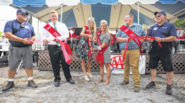 President of Agricultural Society Brad Hoy, left, Junior Fair King Brandon Suever, Queen Ashley Huck, Princess Devyn Hopkins, Prince Zachary Zwiebel and fair manager Bob Fricke cut the ribbon for the opening of the 2019 Allen County Fair on Friday evening.