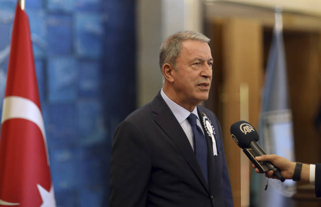 Turkey's Defense Minister Hulusi Akar speaks to the media at the National Defence University, in Istanbul, Wednesday, Oct. 9, 2019. Akar says preparations for an expected Turkish incursion into Syria are continuing. (Turkish Defense Ministry via AP, Pool)