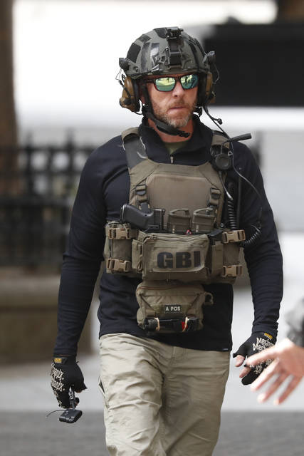 A Georgia Bureau of Investigation bomb technician carries a security tag found in a garbage can in Atlanta Friday, Oct. 18, 2019. A person reported a beeping sound coming from the trash bin outside a state government building in the heart of downtown Police evacuated the building and summoned bomb technicians. (AP Photo/John Bazemore)