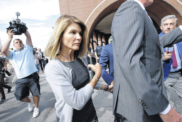 Actress Lori Loughlin departs federal court in Boston in August after a hearing in a nationwide college admissions bribery scandal. Loughlin, her fashion designer husband, Mossimo Giannulli, and nine other parents face new charges in the college admissions scandal. Federal prosecutors announced Tuesday that the parents were indicted on charges of conspiracy to commit federal program bribery.