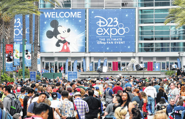 A crowd of people wait to enter the D23 Expo in 2017 as crews do interviews outside the Anaheim Convention Center in Anaheim, Calif. Members of Disney's free D23 fan club were eligible to buy three years of Disney Plus service up front for the price of two years. Other providers dangled freebies to try to encourage growth of their new streaming services.