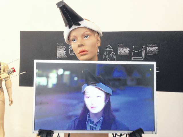 """This 2017 photo provided by artist Jing-cai Liu shows her work titled """"Wearable Face Projector"""" at a gallery in Utrecht, Netherlands. A 2017 video by Liu showing her demonstrating the conceptual art piece, on screen at center, began circulating widely on social media in early October 2019 after Hong Kong instituted an emergency ordinance to ban masks at rallies. Liu said her piece was not intended to be political. She found out that people were sharing her video in relation to the protests when her friends began tagging her in posts with the false caption claiming that protesters in Hong Kong use wearable face projectors to disable the facial recognition system used by the government."""
