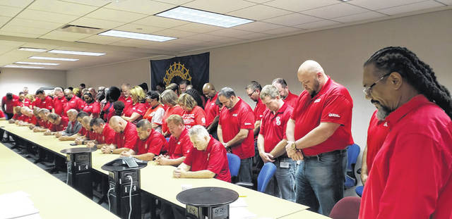 "The UAW's elected bargaining committee stand ""solidarity strong"" at the main bargaining table where they are negotiating with General Motors bargainers for a new tentative agreement."