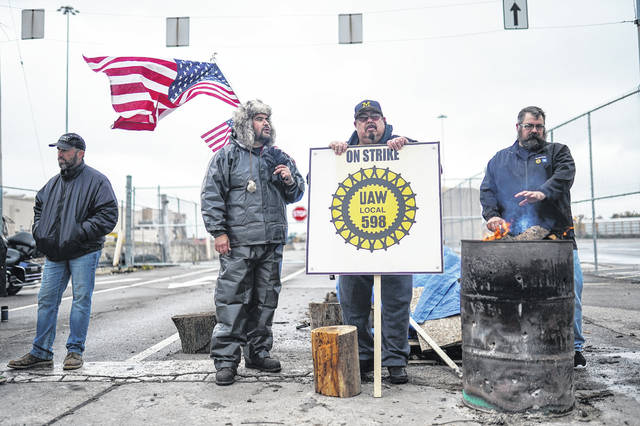 Flint Assembly electrician Mike Perez, center left, of Saginaw, and Flint Assembly Electrician Alex Rodriguez, center right, of Detroit, talk while standing on strike at the north gate of General Motors Flint Assembly on Oct. 16. Many GM workers could be back to work on Monday after ratifying a deal Friday.
