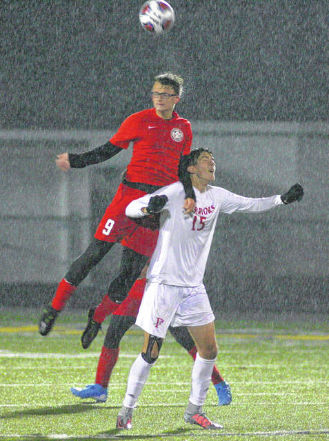 Bluffton's Eli Lemley skies above Fairview Park Fairview's David Nemeth for the header during Wednesday night's Division III regional semifinal in Sandusky.