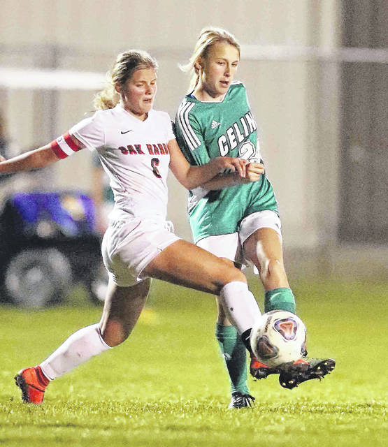 Celina's Kira Dirksen, right, and Oak Harbor's Erica Winters fight for control of the ball during Tuesday night's Division ll regional semifinal at Findlay High School.