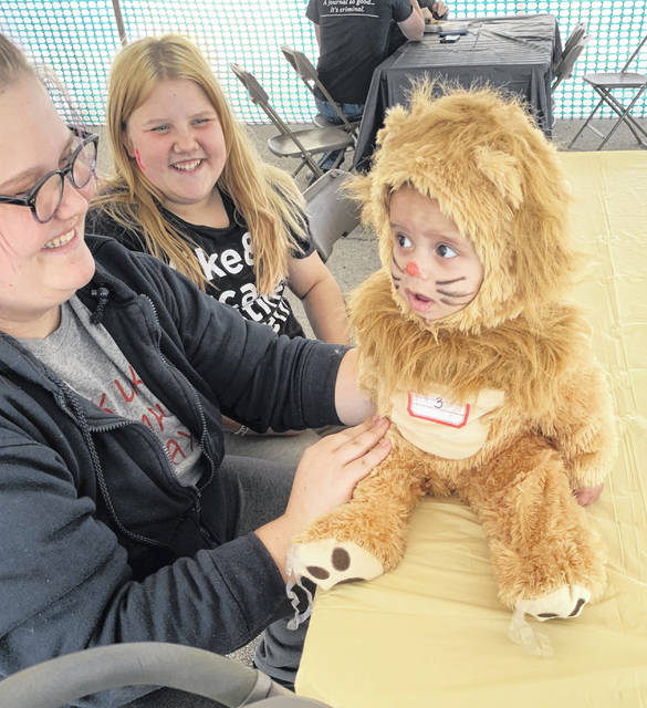 Aubrey Purdy, of Lima, dressed Knyko Watson, 15 months, in a lion costume for Saturday's costume contest at the Lima Mall.