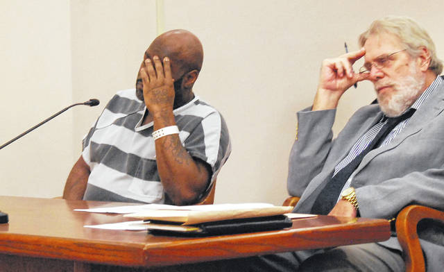 Eric Adams, 41, hides his face during a pre-trial hearing Wednesday in Allen County Common Pleas Court. Adams faces two counts of rape for an alleged incident involving a 16-year-old girl that prosecutors say took place in Lima in 2009. He is shown with his attorney, William Kluge.