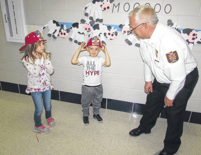Sadie Buckland and Anthony Kropaczewski, Ottawa Elementary School kindergarteners, talk to Ottawa Volunteer Fire Department chief Dan Rieman Friday at the school.