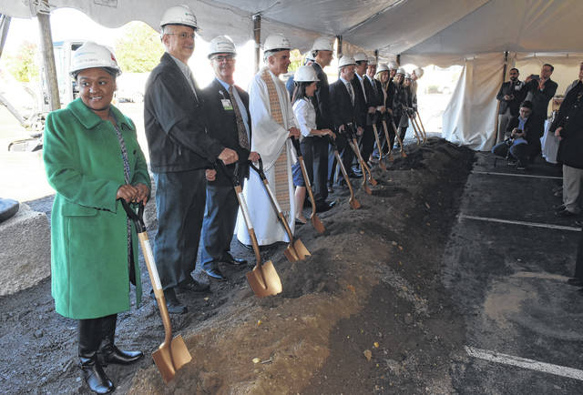 Sharetta Smith, left, Chief of Staff for the City of Lima, and several others pose for a photo after breaking ground for St. Rita's Graduate Medical Education Center on Monday morning.