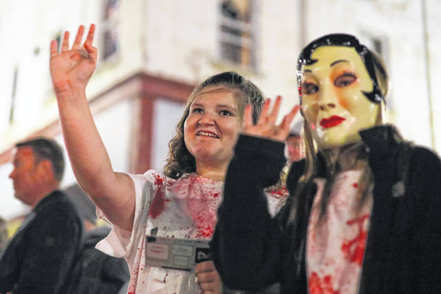 Thirteen year-old Adison Harshbarger (left) of Wapakoneta and 11-year-old Makayla Harshbarger wave to friends in the Halloween Parade in Downtown Wapakoneta on Thursday evening.
