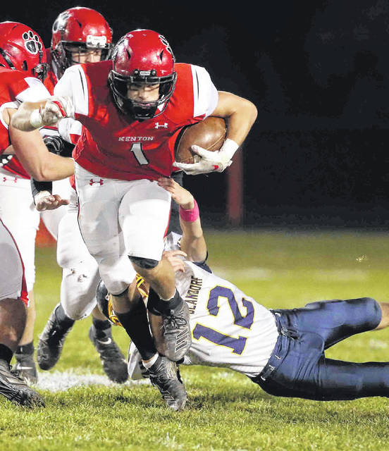 Kenton's Jayden Cornell tries to get clear of Ottawa-Glandorf's Cy Rump during Friday night's game at Robinson Field in Kenton.