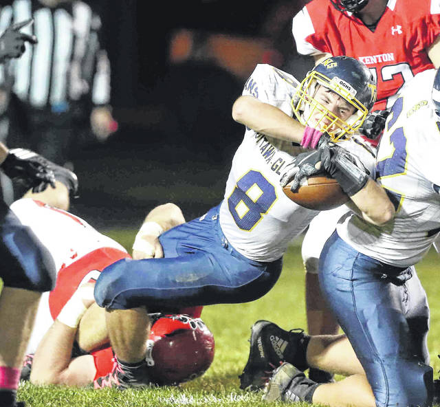 Ottawa-Glandorf's Eric Heebsh stretches for yardage while Kenton's Austin Moore tries to secure a tackle during Friday night's game at Robinson Field in Kenton.