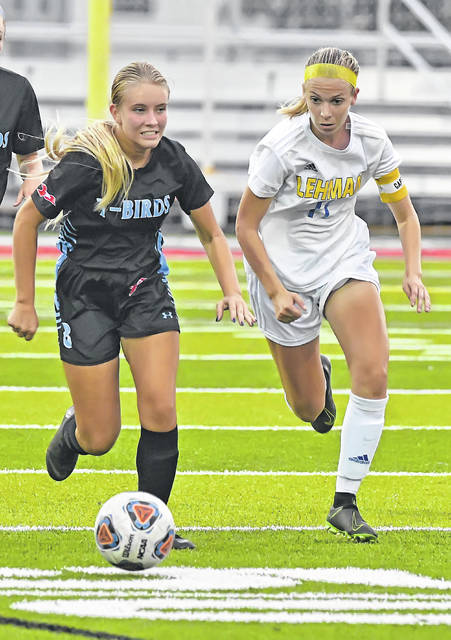 Lima Central Catholic's Megan Latham, left, and Lehman Catholic's Lyndsey Jones compete for the ball during Wednesday's match at Spartan Stadium.