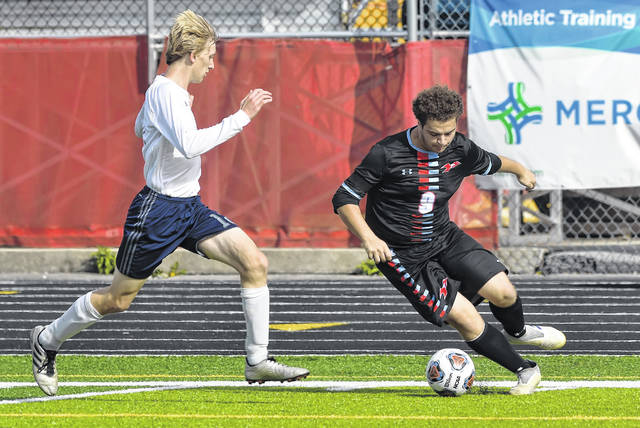 Lima Central Catholic's Brayden Truex dribbles against Temple Christian's Darrick Clay during Saturday's Division III sectional final at Spartan Stadium.