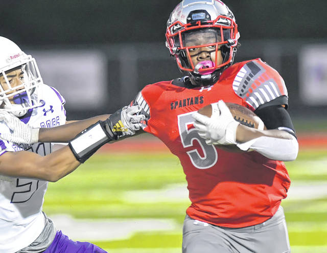 Lima Senior's Jawan Anderson tires to fend off Fremont Ross' Thomas Gluth during Friday's game at Spartan Stadium.