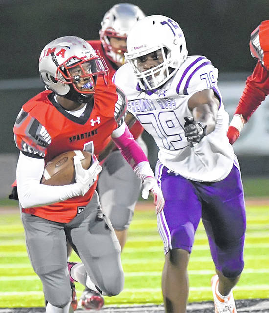 Lima Senior's Cecil Benton Jr. looks to keep away Fremont Ross' Marcus Peters during Friday night's game at Spartan Stadium.