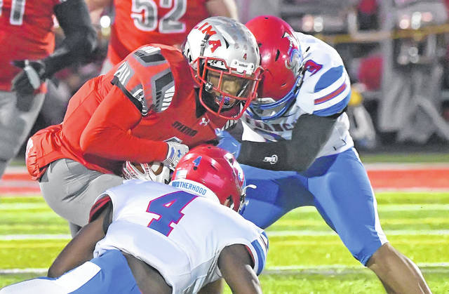 Lima Senior's Cecil Benton Jr. fights for yardage against Toledo St. Francis' Todd Bumphis, left, and Julian Howard during Friday night's game at Spartan Stadium.