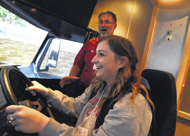 McKenzie Berry, 18, of Van Wert High School, drives a truck simulator with guidance from Bill Goins of the American Trucking Association at 2019 MakerFest at Allen County Fairgrounds on Friday morning.