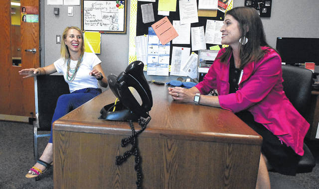 "Kristy Daniels, left, with Colleen Holman-Bodin share a laugh about their entangled families while in Holman-Bodin's office at Benjamin Logan Elementary School. ""It's a scary thought, letting somebody carry your children,"" Daniels said."