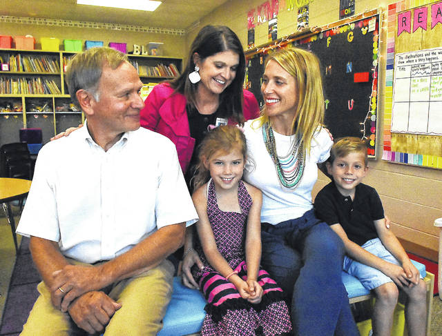 "Colleen Holman-Bodin, middle, decided to be a surrogate mother for her friend Kristy Daniels, second from right. That led to Dr. Jay Meyer, left, delivering Chandler and Chase five years ago. The twins now attend Benjamin Logan Elementary School, where Holman-Bodin is the principal. ""They still hug me every time they see me, which starts a chain of hugs because their classmates think they're supposed to hug me too,"" Holman-Bodin said."