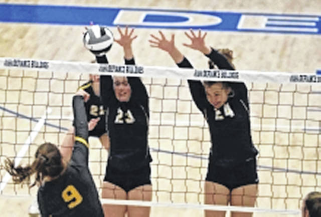 Ottawa-Glandorf's Miya Ellerbrock, left, and Ottawa-Glandorf Erin Kaufman defend the spike of Fairview's Kiersten Cline during Thursday night's Division III district final at Defiance High School.