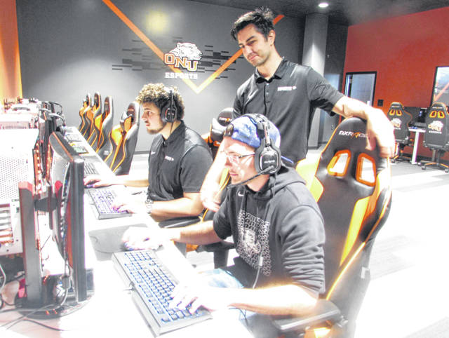 From left are Zach Rondeau, Ohio Northern University student, Troy Chiefari, ONU ESports coach, and Jace Addis, ONU student, playing an Esports video game in the university's Esports arena.